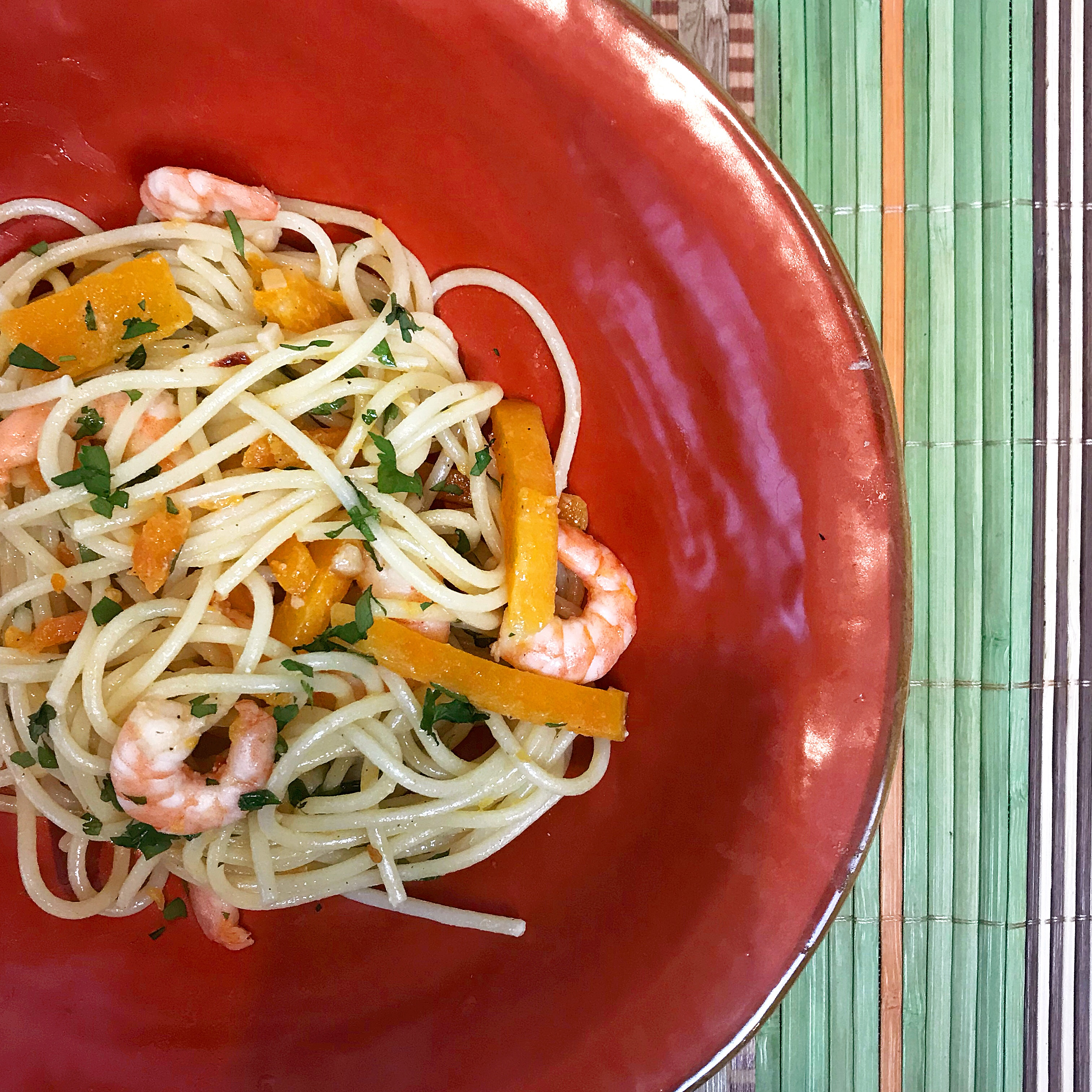 A red bowl of spaghetti and pasta with sliced butternut squash and prawns