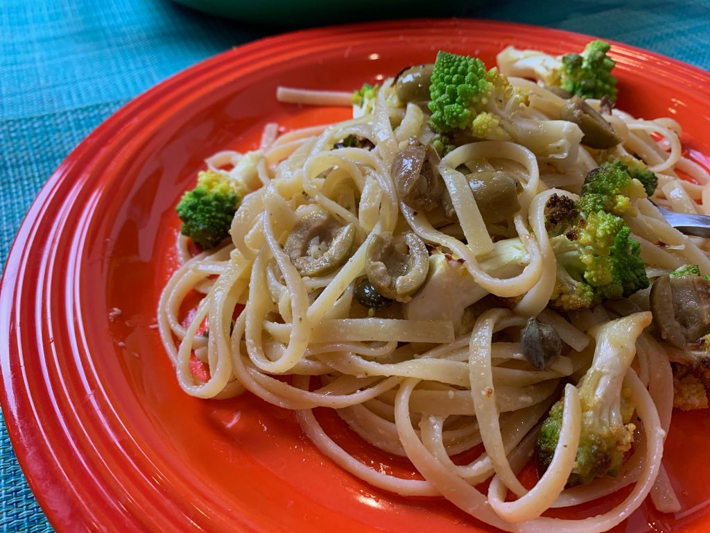 Side angle view of linguine tossed with broccoli, olives, capers and lemon on a bright orange dinner plate.