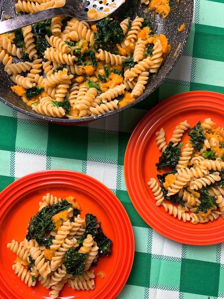 two orange plates with spiral pasta coasted in butternut squash and cavolo nero. On a green check tablecloth