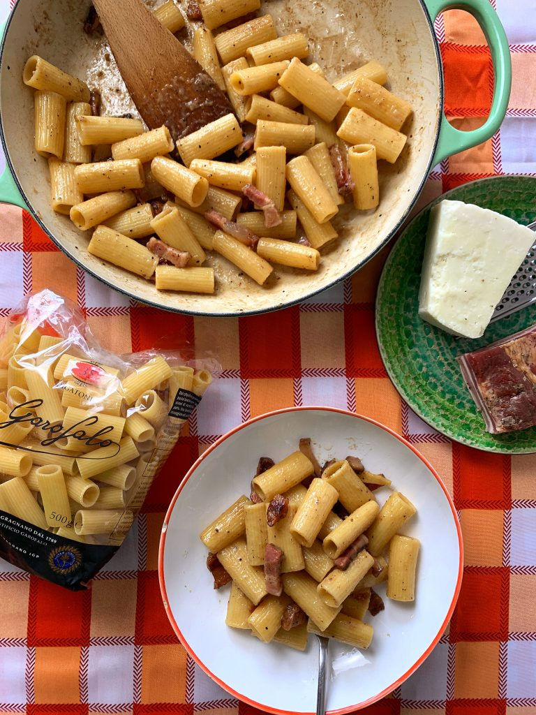 rigatoni alla gricia in a pasta bowl, in a large frying pan with a bag of Garofalo rigatoni, pecorino romano and guanciale on an orange checked table cloth